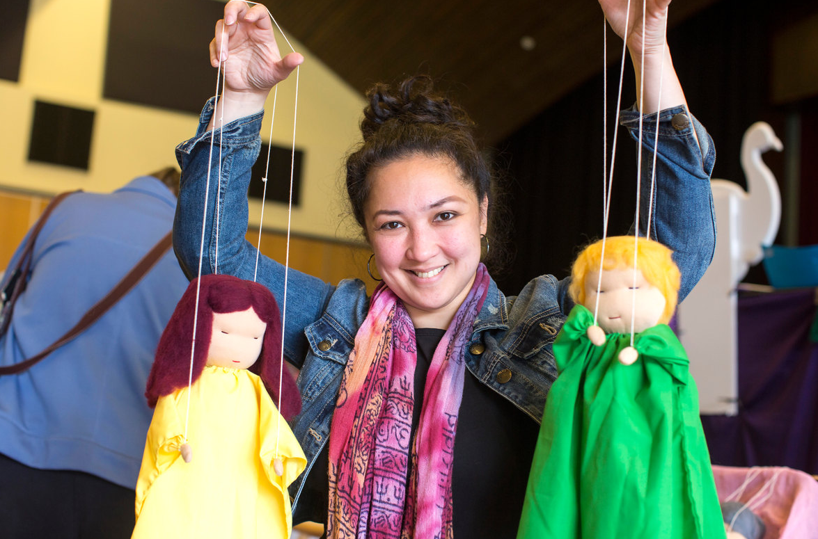 woman holding up puppets